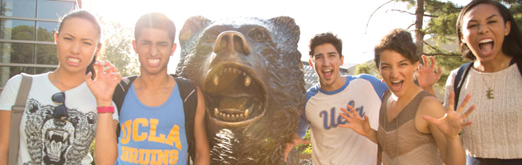 Students gather around bear statue.